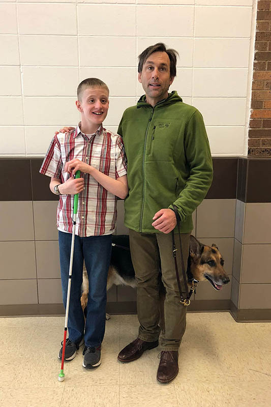 photo of erik weihenmayer with a blind student at spirit lake school