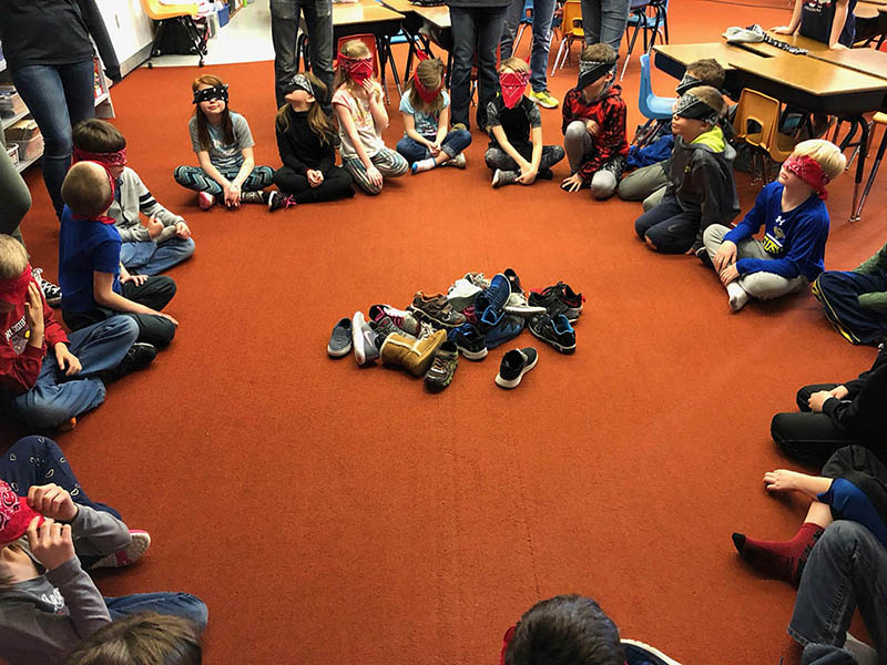 a photo of students blindfolded for whos shoe activity with pile of shoes in center of circle