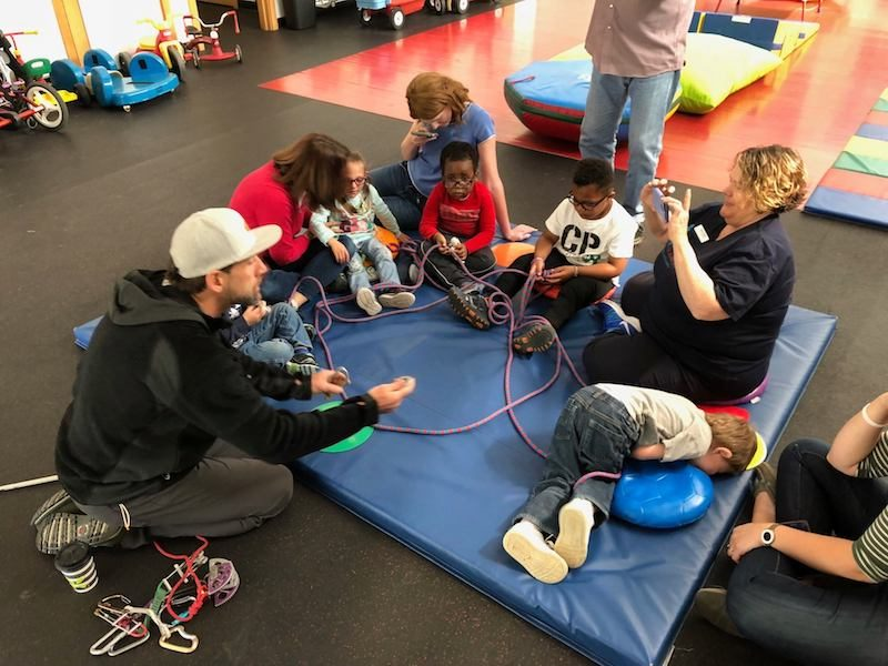 photo of erik weihenmayer on floor with kids at anchor center playing with climbing rope
