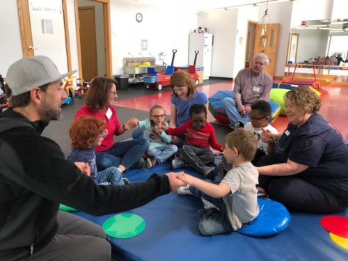 a photo of erik weihenmayer at the anchor center holding hands with small kids in a circle