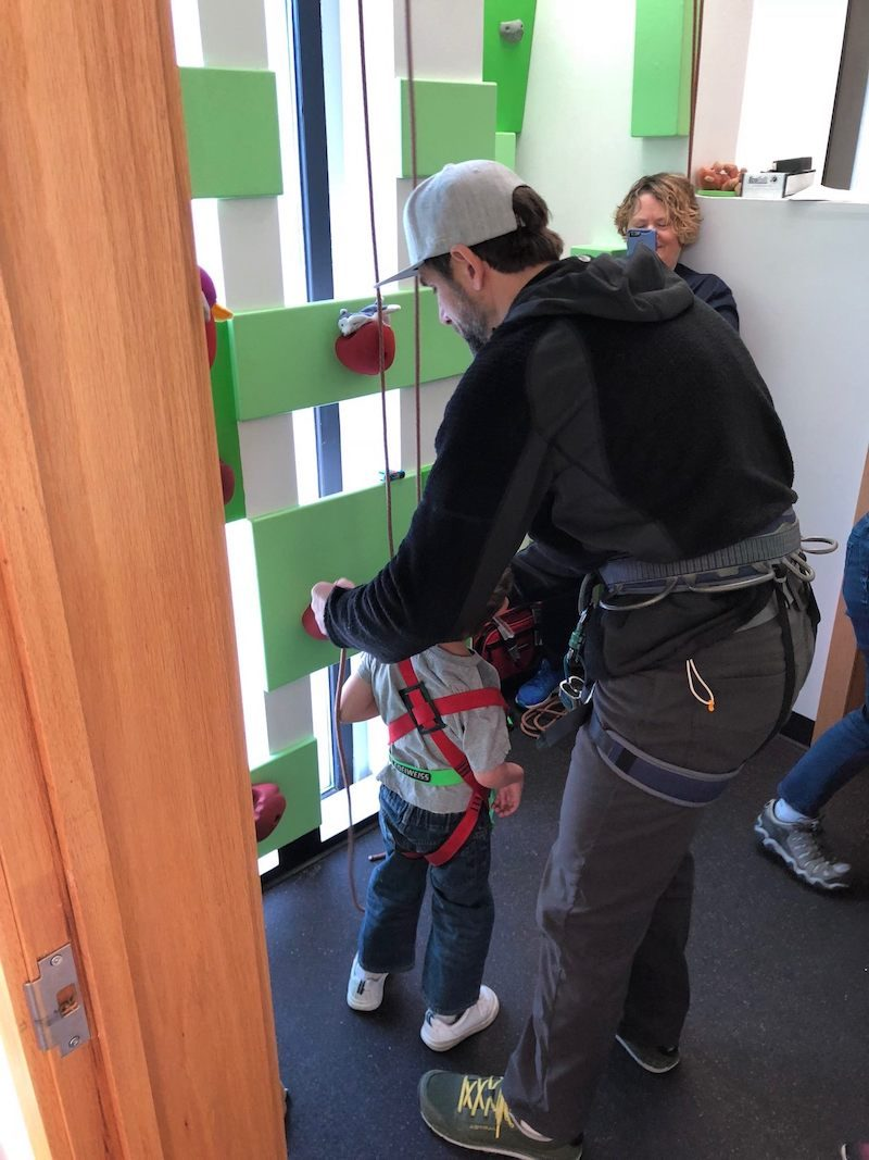 a photo of erik weihenmayer showing a small kid how to climb on a climbing wall
