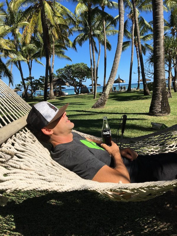 a photo of erik weihenmayer in a hammock with hat over his eyes holding a coca cola beverage