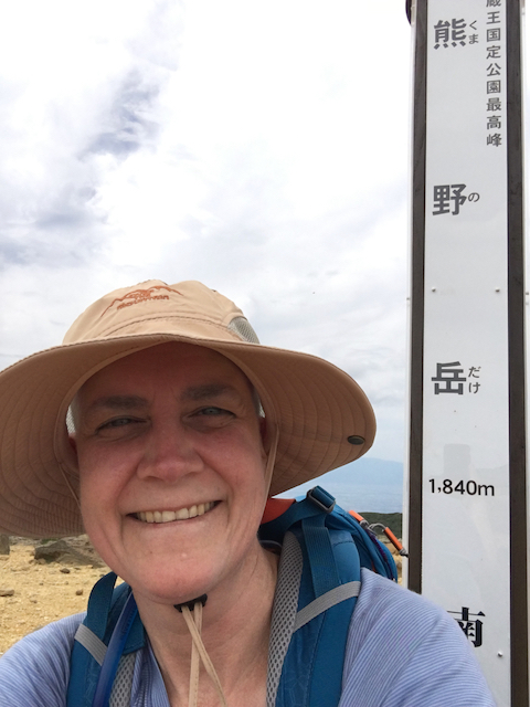 a closeup photo of susan on the summit of mount zao where you can see her almost bald head under her hiking hat