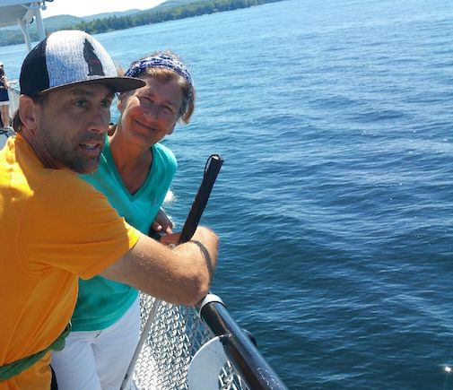 a photo of erik weihenmayer and his wife ellie on railing of boat of lake winnipesaukee