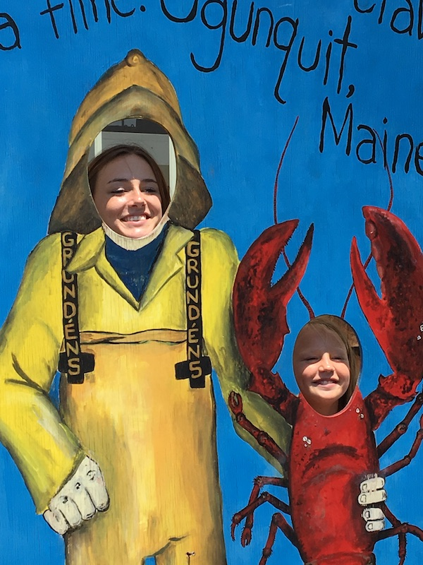 a photo of eriks daughter emma and her little cousin posing behind cardboard images of a lobsterman and a lobster