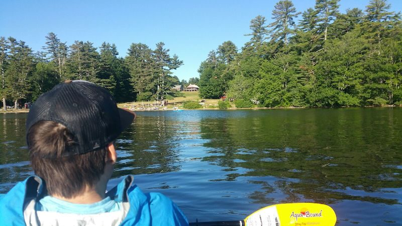 a photo of erik from behind on a tandem kayak on a lake