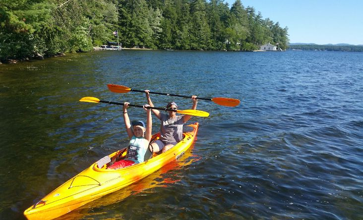 a photo of two people holding up kayak paddles on a lake