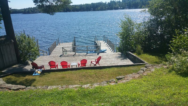 a photo of a dock overlooking a lake with adirondack chairs