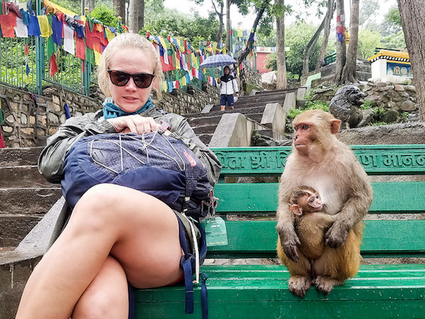 a photo of a girl and a monkey on a bench in nepal