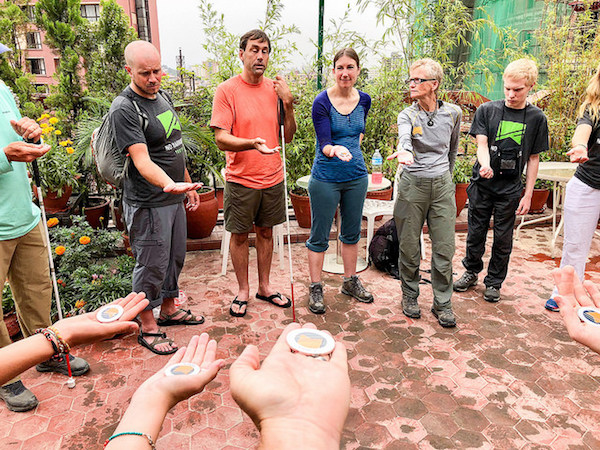 a photo of erik weihenmayer and participants circled up for a no barriers coin ceremony at close of trip in nepal