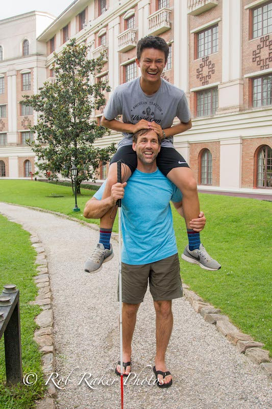 a photo of erik weihenmayer with his son arjun on his shoulders as a teenager