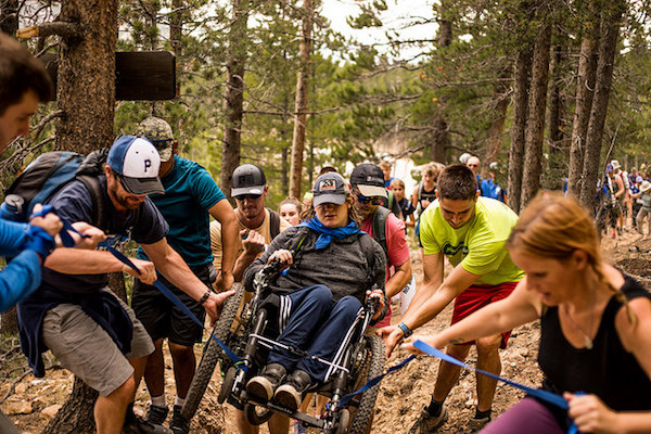 a photo of connor in his wheelchair being helped up the trail with folks using pulleys