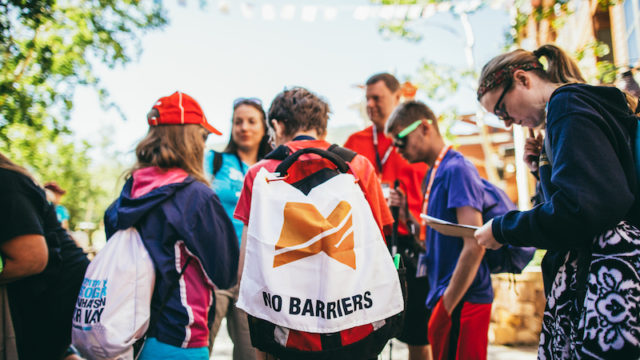a photo of a group of kids with a no barriers flag huddling up for a scavenger hunt