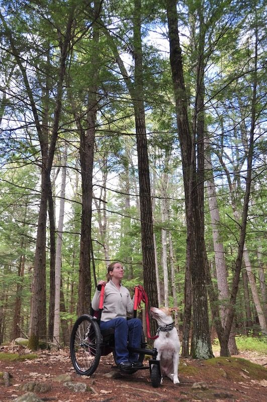 a photo of nerissa with her dog in the woods