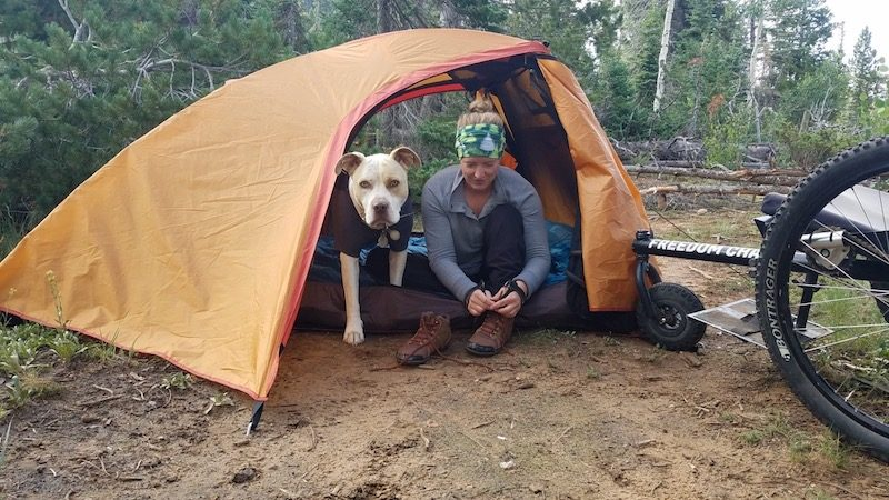 a photo of nerissa with her dog in a tent on a camping trip
