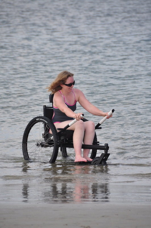 a photo of nerissa in her wheelchair in the water on a beach