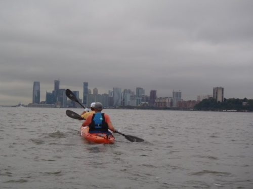 a photo of erik weihenmayer kayaking around nyc with new jersey on his right and statue of liberty up ahead