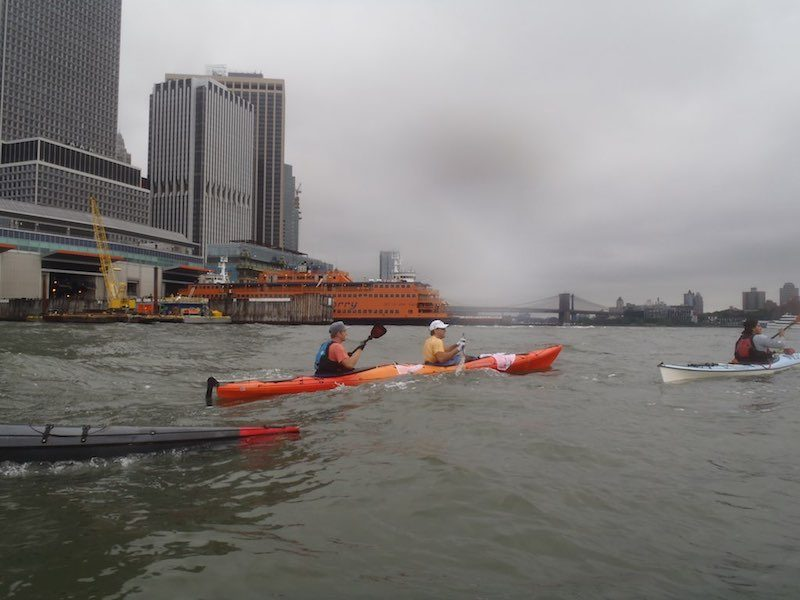 a photo of erik weihenmayer kayaking the hudson river with the staten island ferry and brooklyn bridge in distance