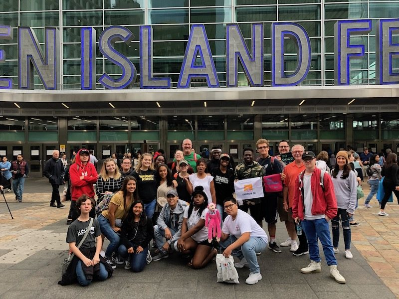 a photo of kids posed in a group shot in front of staten island ferry sign