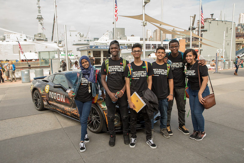 a group of youth pose together in front of sam car on the intrepid at the no barriers summit in nyc
