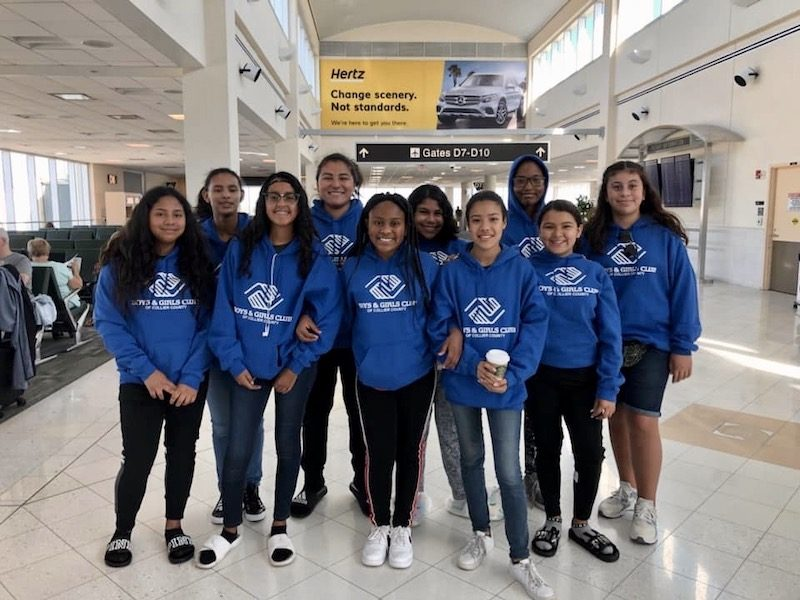 a group of girls posed in an airport smiling with sweatshirts that all say boys and girls club