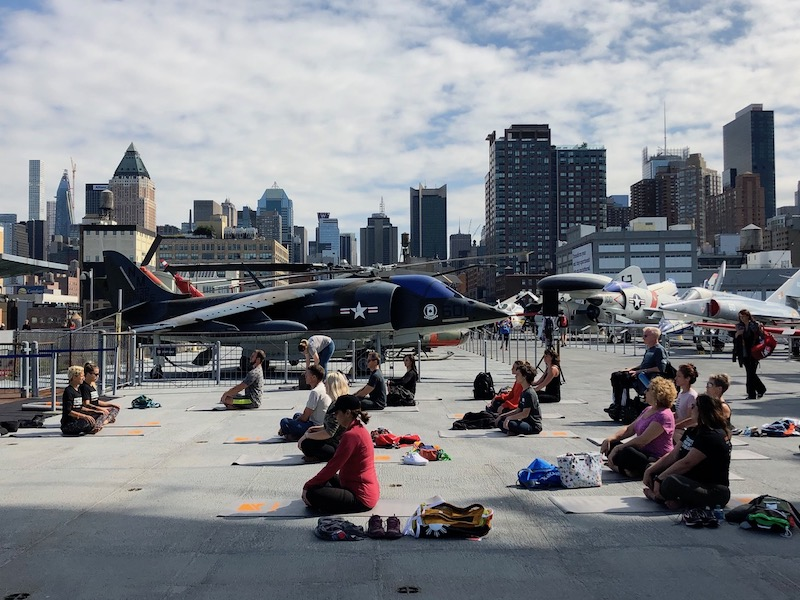 a shot of yoga on the intrepid in nyc for the no barriers summit