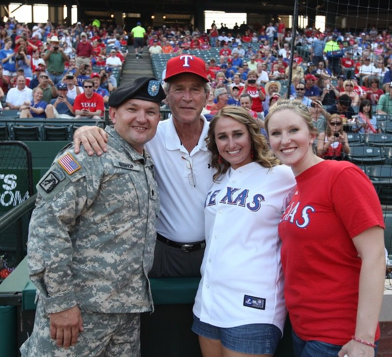a photo of james bishop in his army uniform at a baseball game with george w bush and two females