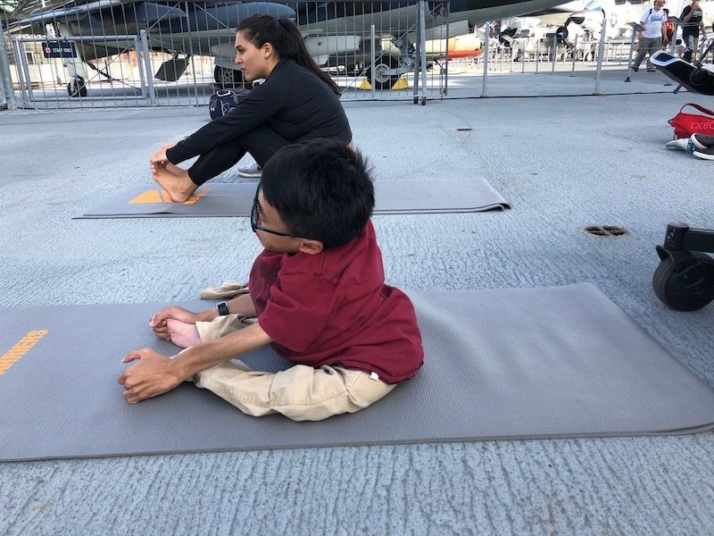 a photo of karl on his mat doing yoga at the no barriers summit