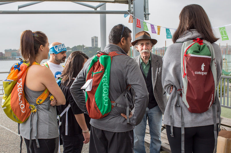 a photo of a group of folks with backpacks listening to directions