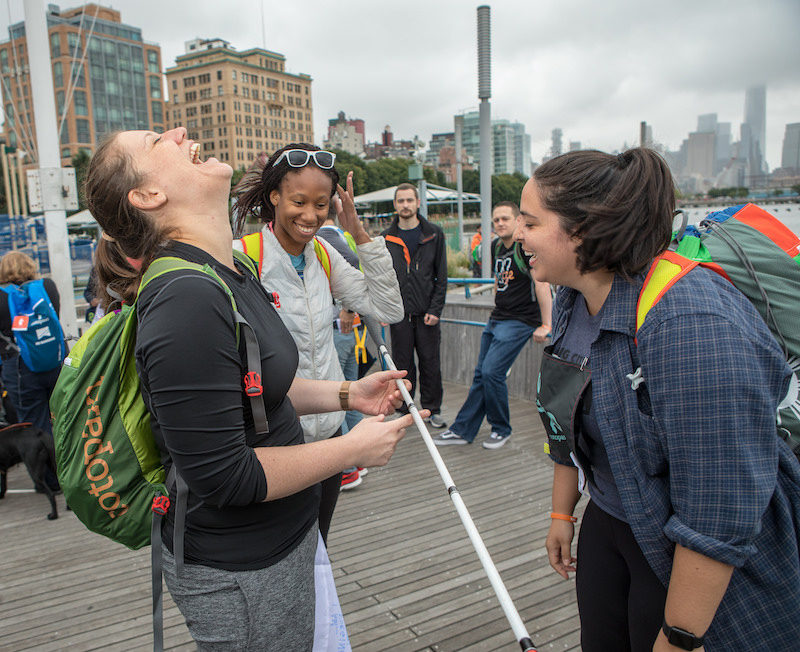 a photo of three girls who are laughing at the no barriers summit in nyc