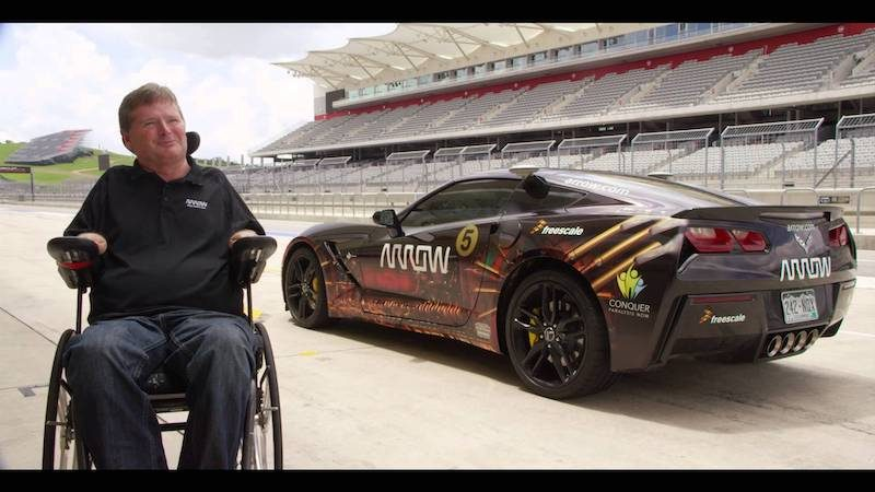 a photo of sam schmidt in a wheelchair next to his corvette stingray the sam car on a race car track