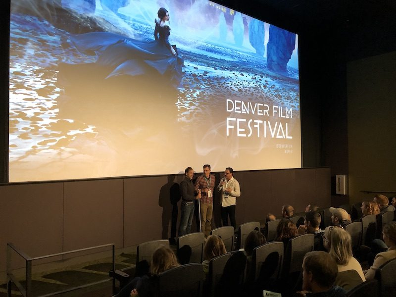 a photo of erik with michael brown answering questions in front of the movie screen after the denver film festival showing