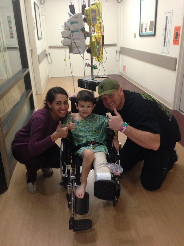 a photo of hunter in a wheelchair post opp with his mom and dad all giving thumbs up