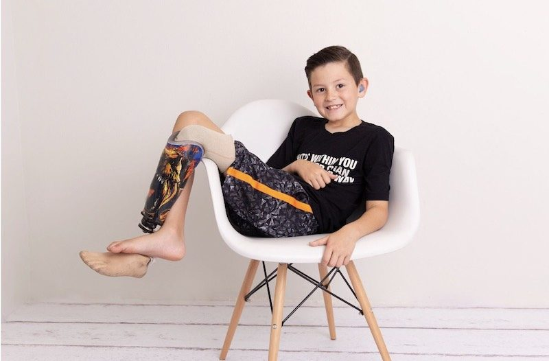 a photo of hunter lounging in a chair at a photo shoot in his no barriers t shirt