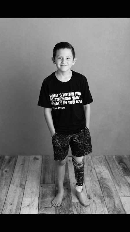 a black and white photo of hunter posing at a photo shoot wearing his no barriers shirt