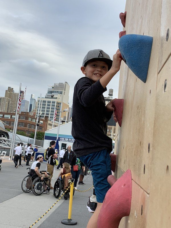 a photo of hunter climbing up the rock wall at the no barriers summit in nyc
