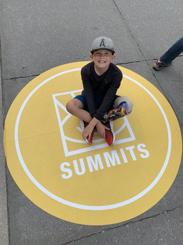 a photo of hunter sitting cross legged on the summits artwork on the ground at the nyc summit