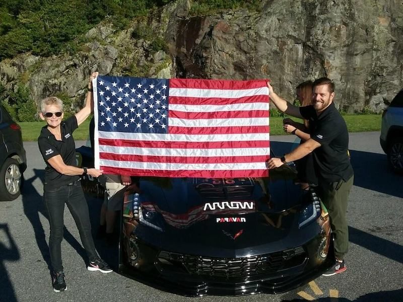 a photo of gretchen evans holding up an american flag with the folks from arrow electronics