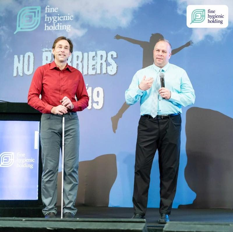 a photo of erik and ceo jim lafferty standing on stage at fhh conference