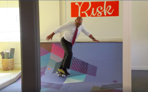a photo of a man in a suit skateboarding in an office with a sign behind him that says risk