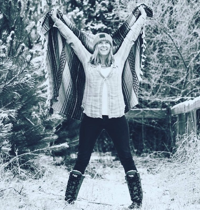 a photo of angie standing in a power pose holding up a blanket behind her