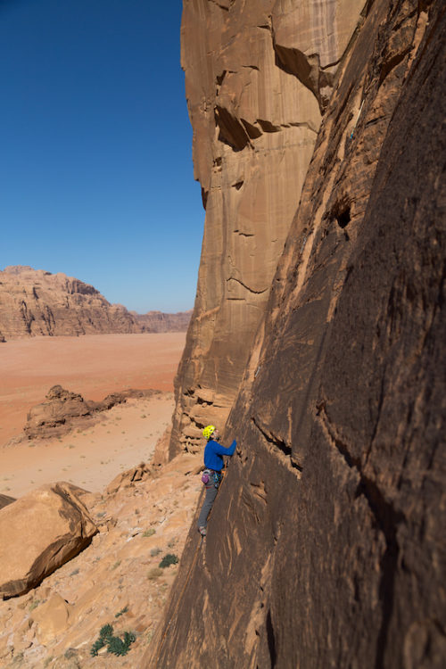 a photo of erik climbing in the desert up a massive wall