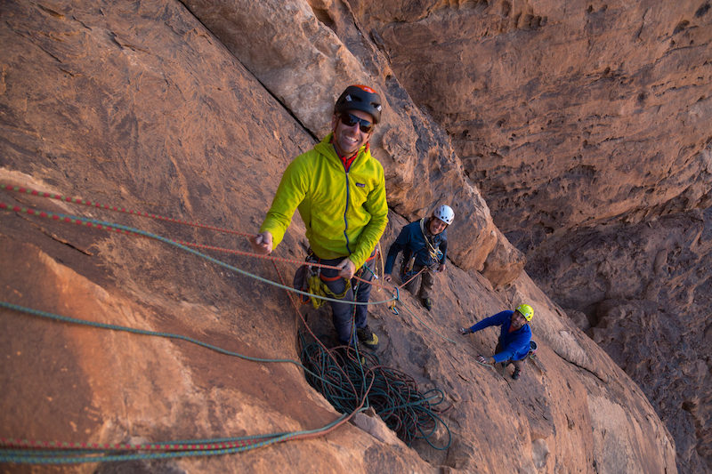 a photo of three guys rock climbing in jordan