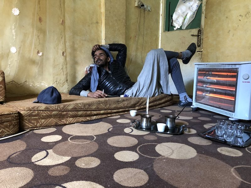 a photo of a man lounging by a heater with tea