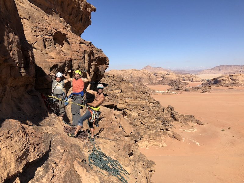 a photo of men flexing while climbing in jordan