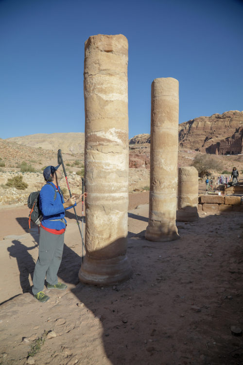 a photo of erik standing next to stone pillars in petra