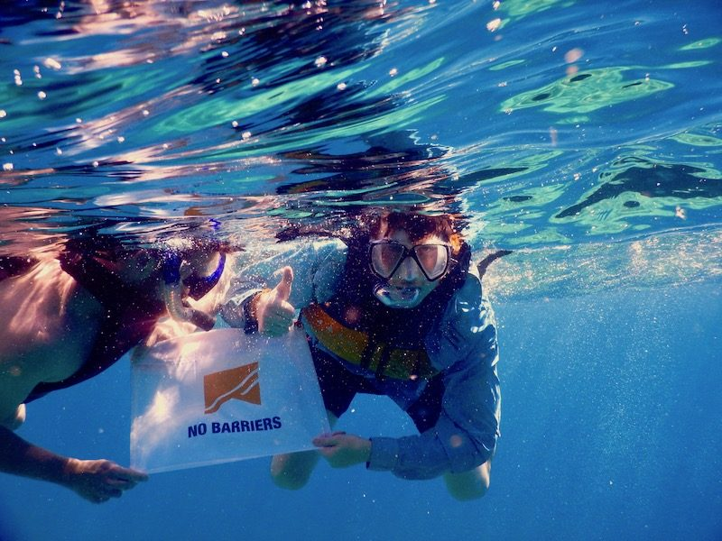 a photo of two men snorkeling with a no barriers flag