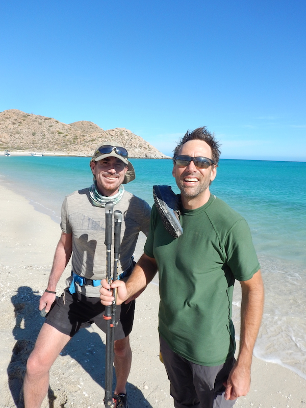 a photo of erik with friend rob harsh on the beach smiling